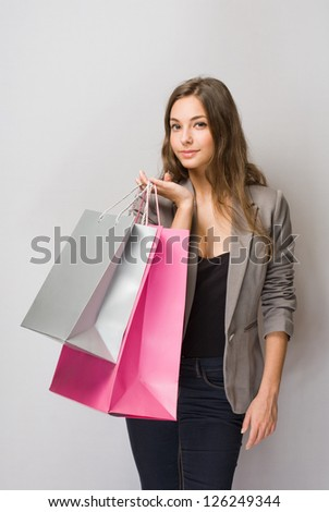Happy young brunette shopper with colorful shopping bags.