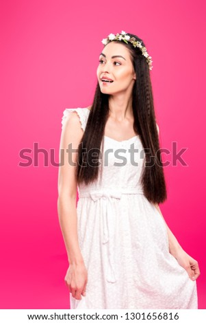 happy young brunette woman in white dress and floral wreath smiling and looking away isolated on pink #1301656816