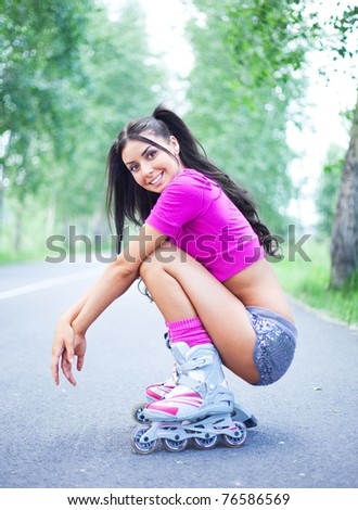 happy young brunette woman on roller skates in the park