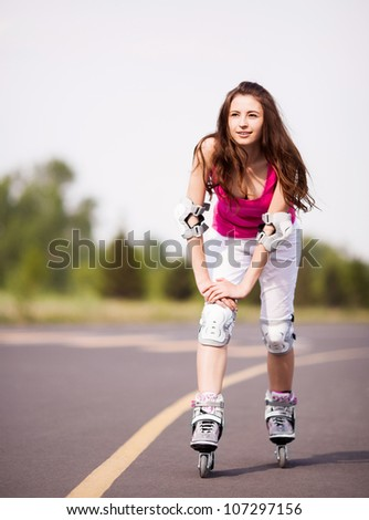 happy young brunette woman roller skating in the park