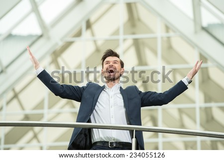 Happy young business man at work in modern office, raised his hands up.