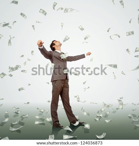 happy young business man enjoying dollar rain
