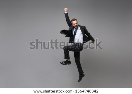 Happy young business man in classic black suit shirt tie posing isolated on grey background. Achievement career wealth business concept. Mock up copy space. Jumping, doing winner gesture, screaming