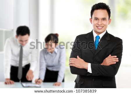 Happy young business man looking at camera with satisfaction at office
