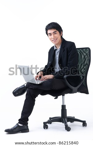 Happy young business man sitting in a chair and  working with laptop