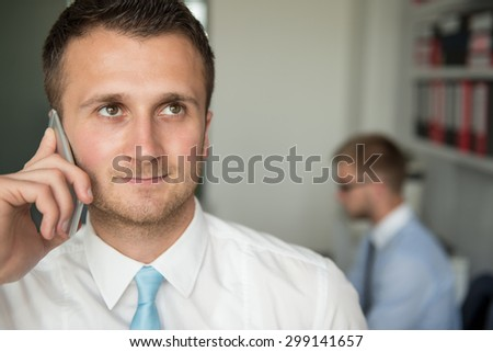 Happy Young Business Man Talking On Telephone In Modern Office Behind Him Sitting His Colleague