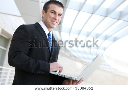 Happy young business man using laptop at office building