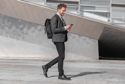 Happy young business man using phone walking on commute commuting to work with backpack bag on city street. Businessman texting looking at smartphone.