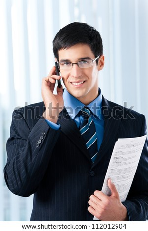Happy young business man with cellphone and documents, at office