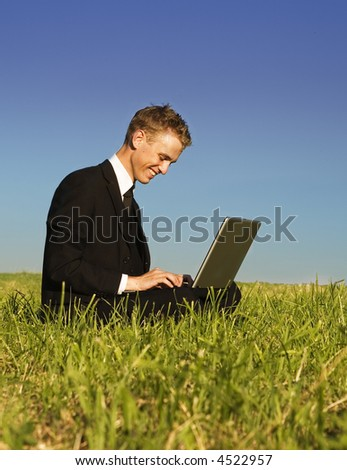 Happy young business man working in the park. Beautiful summer setting with green lawn and deep blue sky.