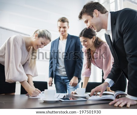 Happy young business people brainstorming at conference table