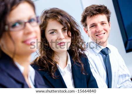 Happy young business people sitting side by side, smiling.