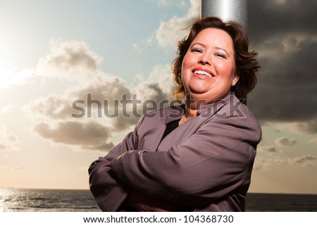 Happy young business woman wearing brown suit. On location. Outdoors. Short brown hair. Blue cloudy sky. Sunset.