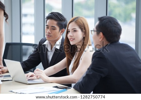 happy young businessman and businesswoman team working together with laptop computer on desk discussing information in office.boss and secretary  discuss at windows glass background #1282750774