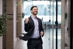 Happy young businessman dancing in office corridor celebrate business success or job promotion, excited male employee enjoy good work results or win, having Friday fun celebration, victory concept