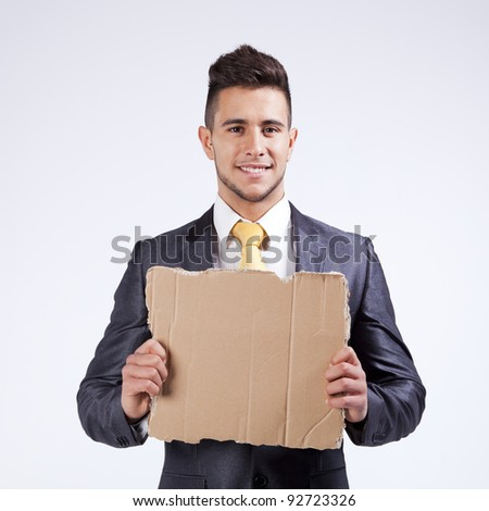 Happy young businessman holding a blank piece of cardboard
