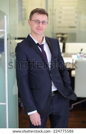 Happy young businessman in black suit stands at entrance to conference hall