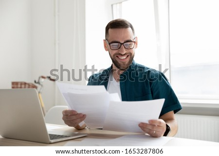 Happy young businessman in glasses looking through paper documents, satisfied with research results. Smiling male accounting manager reviewing financial report, sitting at table alone at office.