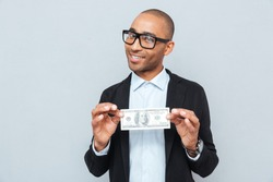 Happy young businessman in glasses smiling and holding dollar banknote