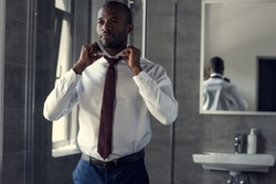 happy young businessman in white shirt putting on his tie at bathroom