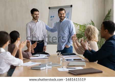 Happy young businessman introduce new male employee newcomer at office meeting, man boss congratulate worker with promotion or achievement, colleagues applaud, acknowledgment concept Foto d'archivio ©