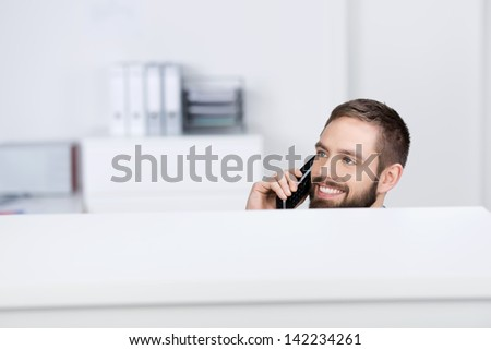 Happy young businessman looking away while on call in office cubicle