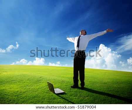 happy young businessman on spring field