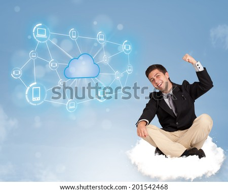 Happy young businessman sitting on cloud with cloud computing