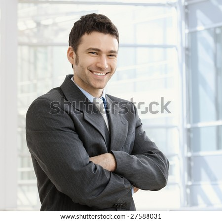 Happy young businessman smiling at office.