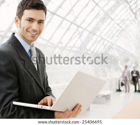 Happy young businessman using laptop in business building, smiling.