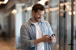Happy young businessman using smart phone standing in office hallway, smiling male professional holding smartphone working with business apps texting sms enjoy corporate technology on mobile device