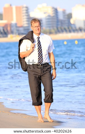 Happy young businessman walks close to the sea
