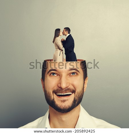 happy young businessman with open head. couple in love kissing and standing in the man\'s head. photo over grey background