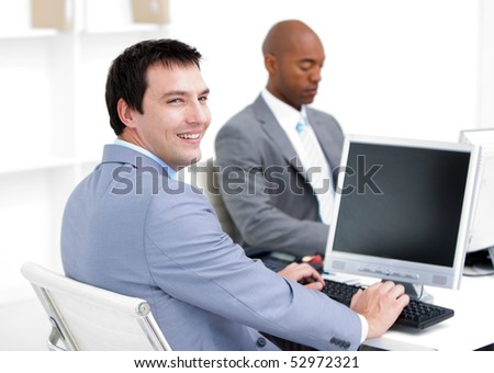 Happy young businessmen working at computers in the office