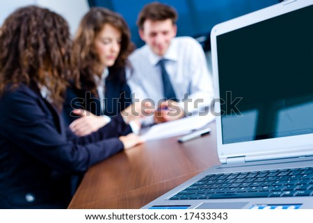 Happy young businesspeople having meeting in board room. Focus placed on laptop screen - space for your text or logo..