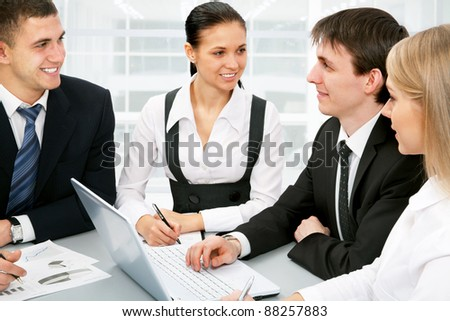 Happy young businesspeople having meeting in boardroom at office