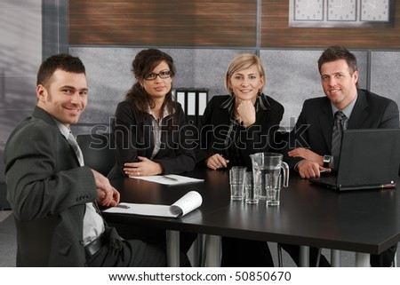 Happy young businesspeople sitting at meeting table in corporate office, looking at camera, smiling.