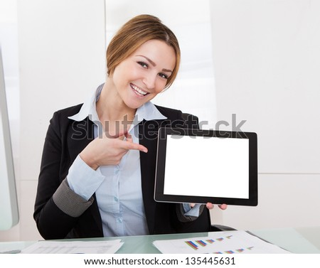 Happy Young Businesswoman Gesturing On Digital Tablet
