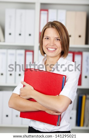 Happy young businesswoman holding a red binder