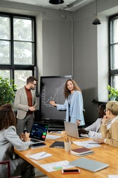 Happy young businesswoman pointing at graph on blackboard during presentation