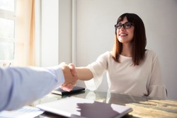 Happy Young Businesswoman Shaking Hand With Her Colleague Over Desk