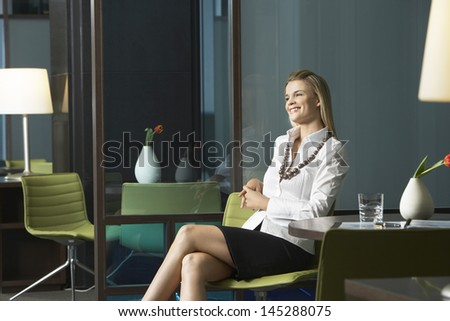Happy young businesswoman sitting in office and smiling