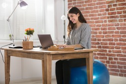 Happy Young Businesswoman Sitting On Fitness Ball Using Laptop In Office