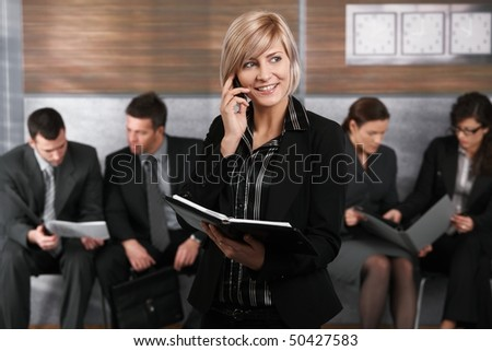 Happy young businesswoman standing in office hallway, holding personal organizer, talking on mobile phone.