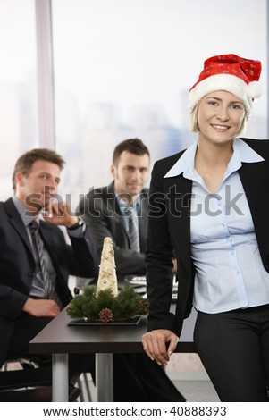 Happy young businesswoman wearing Santa Claus hat at office, looking at camera, smiling. Businessmen in background.