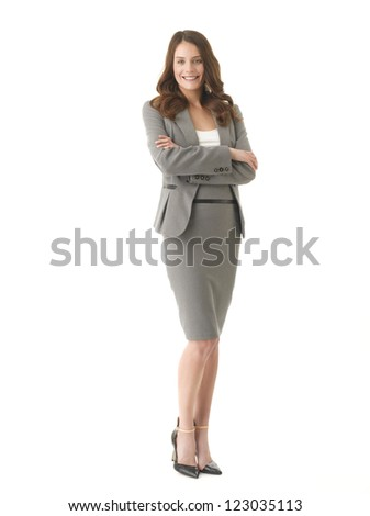 Happy young businesswoman with arms crossed standing against isolated white background
