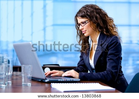 Happy young businesswoman working on laptop computer at office, smiling.
