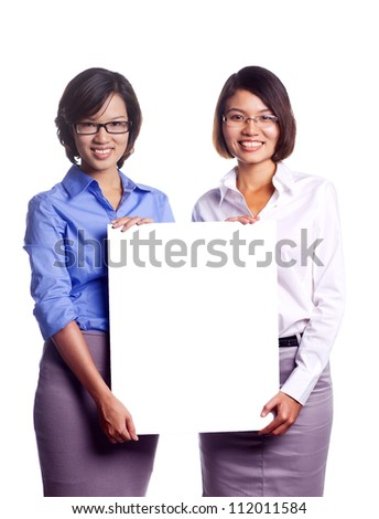 Happy young businesswomen showing blank signboard over white background