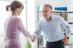 Happy young candidate shaking hands with her employer after a job interview, employment and business meetings concept