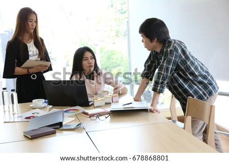 Happy young casual Asian businessman as a meeting leader presenting his work to mixed race colleagues, Businessman as a meeting leader giving presentation in the meeting room high rise building.